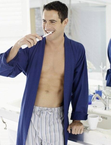 Der Mann putzt mit der Oral-B Bürste