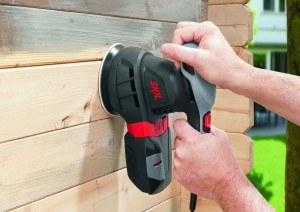 Arbeit des Exzenterschleifers an Holzwand