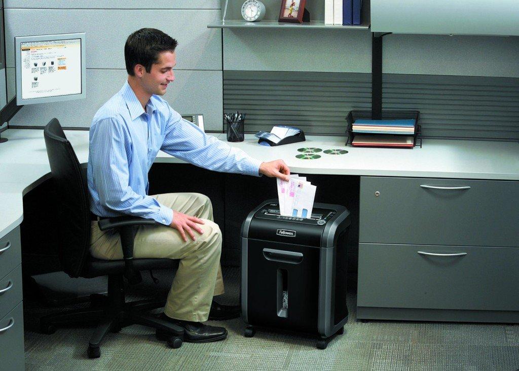 Mann bedient einen Aktenvernichter von Fellowes im Büro