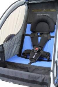 Ein Kind findet bequem und sicher im Fahrradanhänger Sportrex1 von Qeridoo platz.