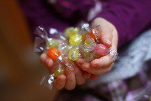 Kinderhände gefüllt mit Bonbons