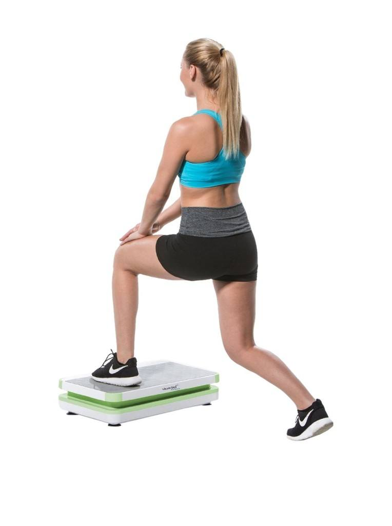 Frau Trainiert Beine auf Skandika Vibrationsplatte