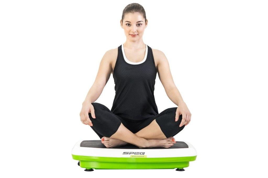 Frau im Schneidersitz auf Speq Vibrationsplatte