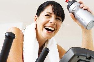 Lachende Frau beim Crosstrainer-Training