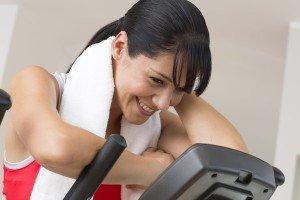 Eine junge Frau trainiert auf einem Ellipsentrainer