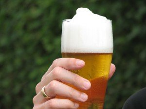 Hand hält Bierglas mit Bier