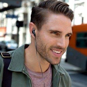 Mann mit In-ear-Kopfhörern am Busbahnhof