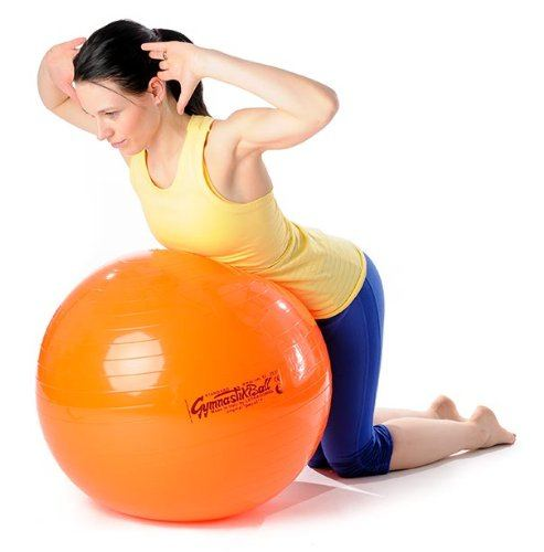 Frau auf Pezziball macht Rückenuebung.