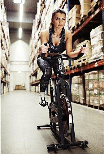 Frau im Lagerhaus auf Fitnessbike.