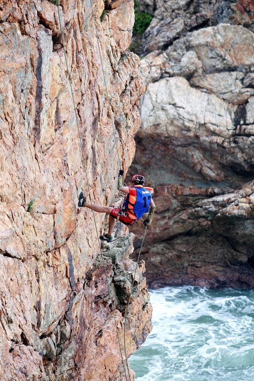 Kletterer seilt sich am Fels ab.