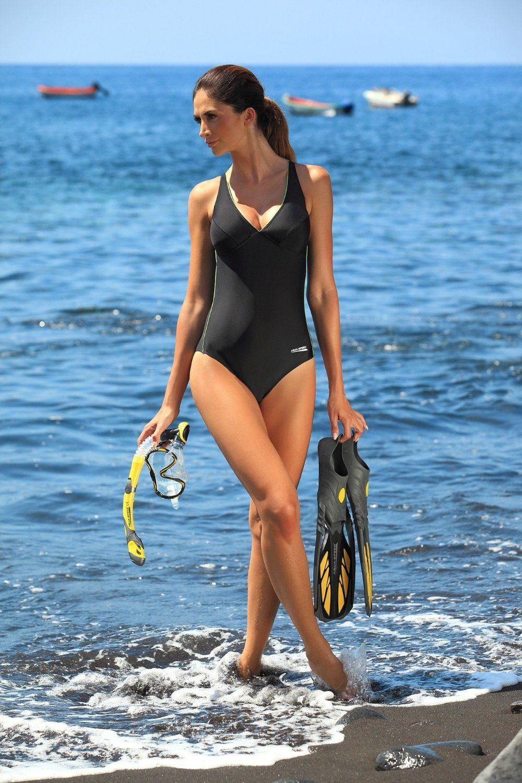 Frau in Badeanzug und Schnorchelset am Strand.