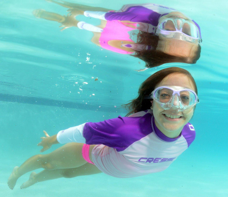 Maedchen schwimmt mit Schnorchelmaske.