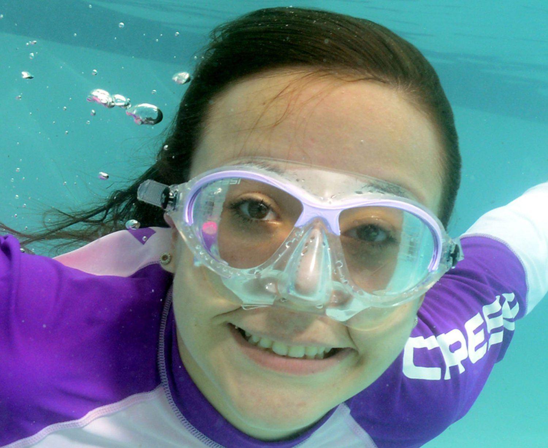 Kind mit Tauchmaske schwimmt.