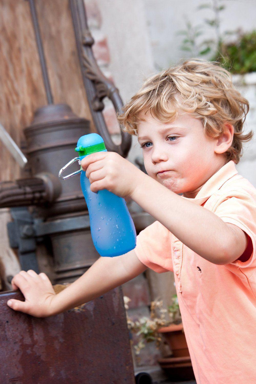 Kind haelt Flasche in der Hand.