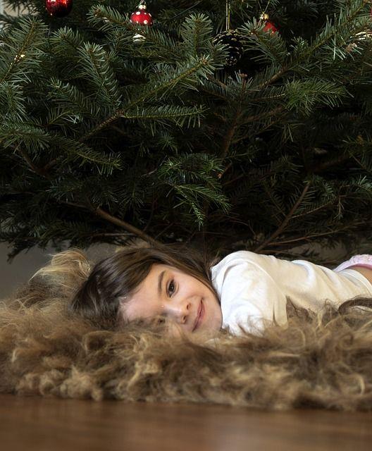 Kind unter Baum mit Weinachtsbaumstaender