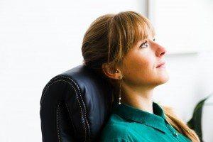 Frau sitzt auf Kings Chefsessel