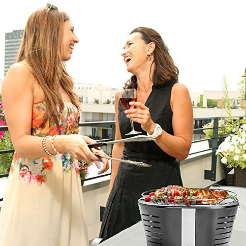 Zwei Damen beim Grillen auf einem Gasgrill auf einer Dachterrasse