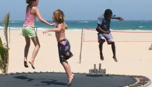 Kinder springen auf einem Trampolin am Strand