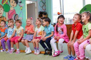 Kinder sitzen im Kindergarten auf einer Bank