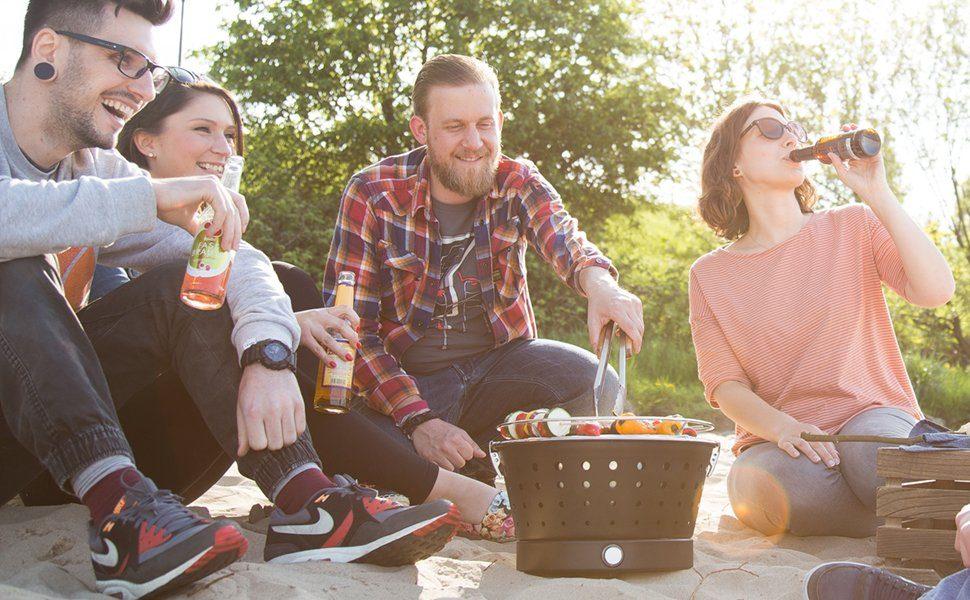 Freunde beim Feiern mit einem Gasgrill im Freien