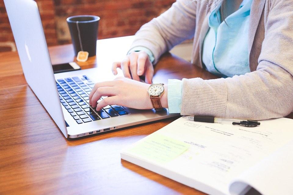 Frau recherchiert vor Kauf Bürostuhl am Laptop