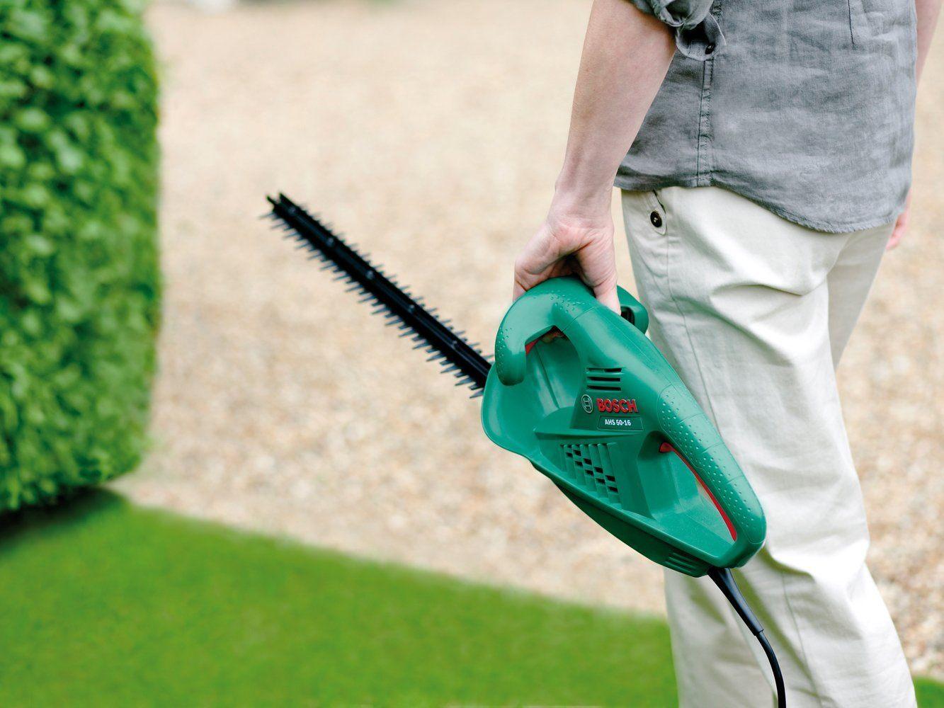 Mann trägt eine Elektro-Heckenschere von Bosch in den Garten