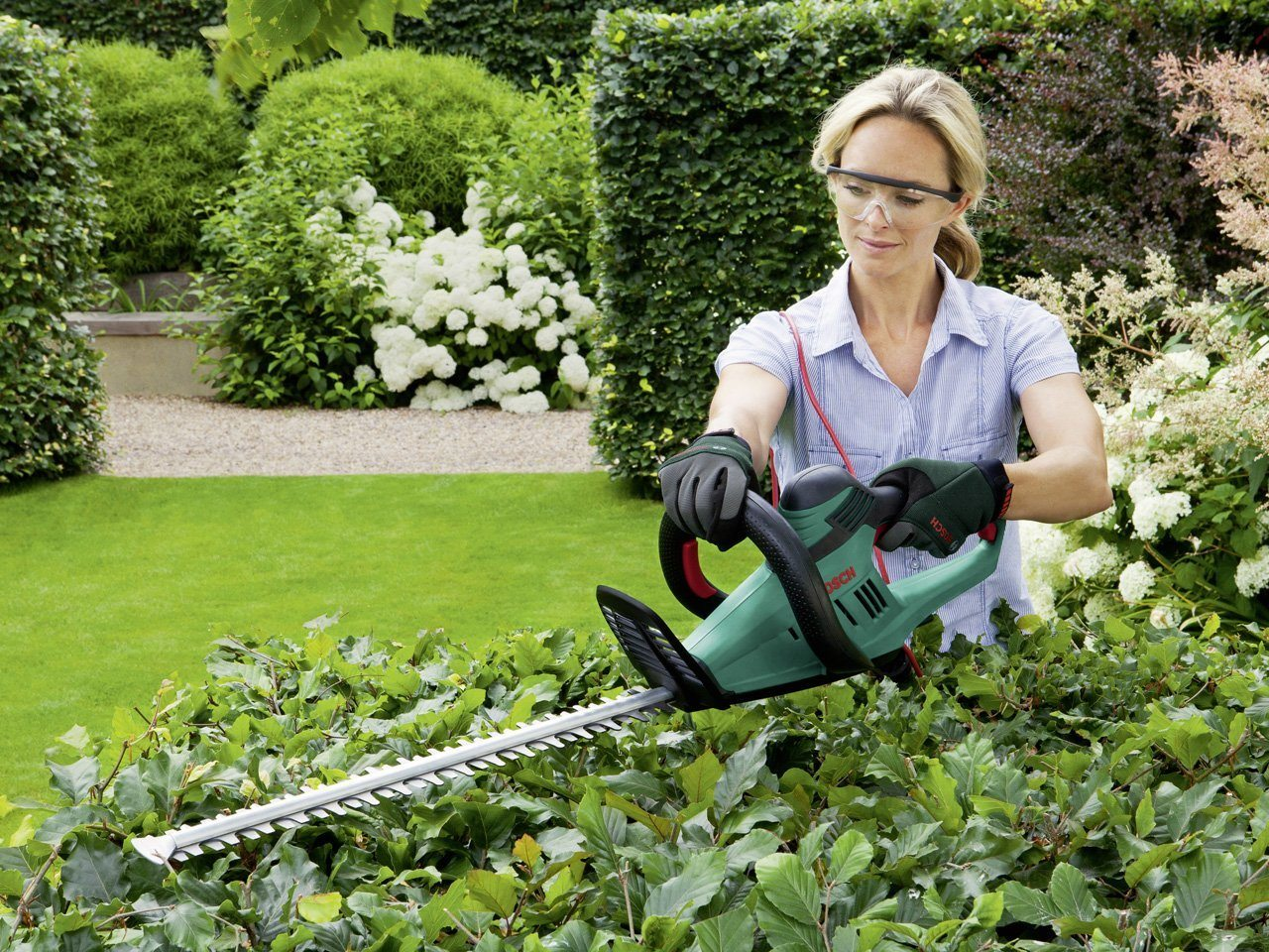 Frau mit einer Elektro-Heckenschere von Bosch bei der Gartenarbeit