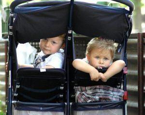 Geschwister in einem Geschwisterkinderwagen sitzen nebeneineander