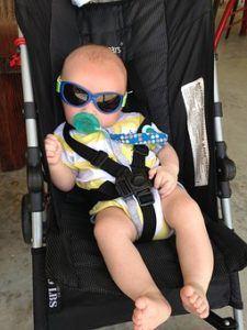 Ansicht von einem Baby mit Sonnenbrille im Buggy
