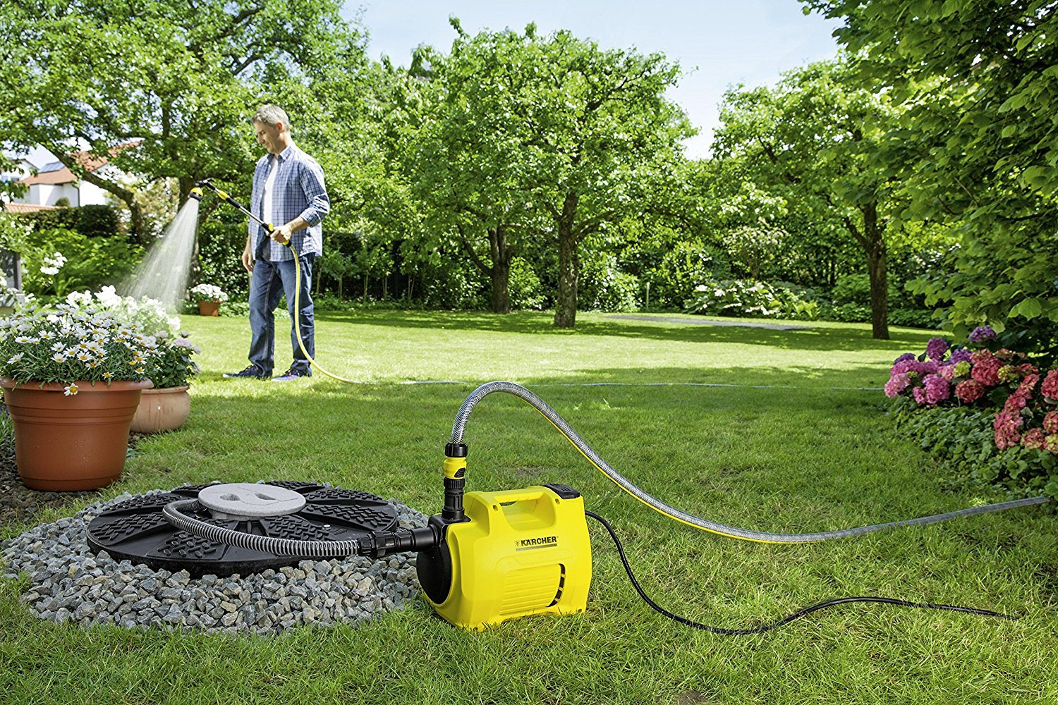 Mann im Garten testet Gartenpumpe