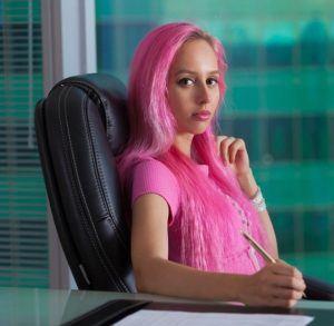 Frau mit pinken Haaren sitzt auf Chefsessel