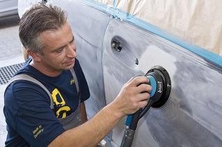 Mann arbeitet am Auto mit Hazet Exzenterschleifer 9033-2 im Test