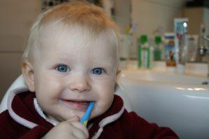 Kleinkind putzt mit einer elektrischen Zahnbürste die Zähne