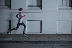 Mann rennt neben Gebäude mit Polar M430 Pulsuhr ohne Brustgurt im Test
