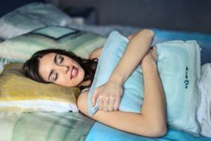 Frau schläft mit ihrem Kissen im Test