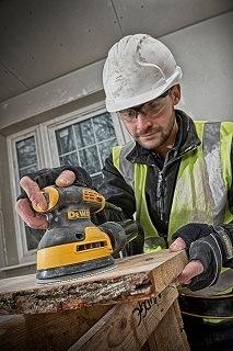 Mann schleift auf Holz mit dem DeWalt Exzenterschleifer DWE6423 im Test