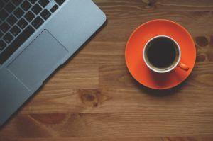 Tasse mit Schwarzem Kaffee neben einem Laptop auf einem Tisch