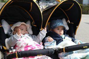 Mädchen und Junge im Zwillingskinderwagen