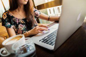 Frau an einem Laptop mit Kaffee
