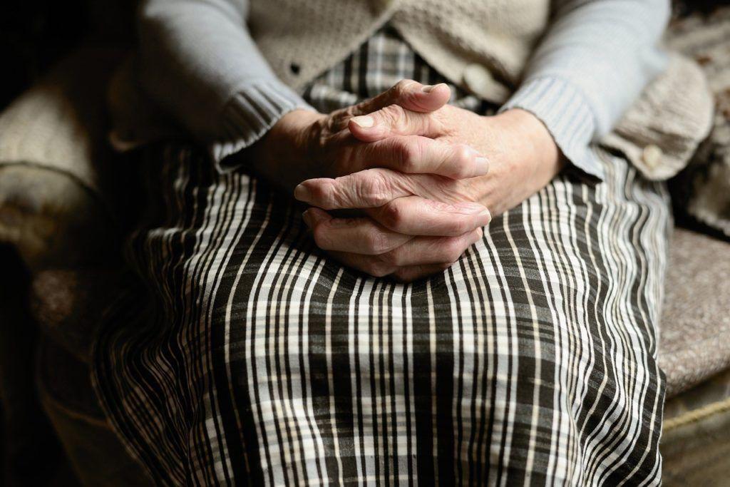 Alte Frau faltet die Hände über ihrem Schoß