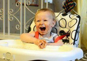 Lachendes Baby in einem Hochstuhl