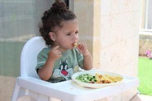 Mädchen im Hochstuhl isst Gemüse