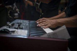 Hände eines Musikers über einem e-piano