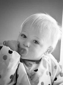 Baby mit Löffel auf dem Hochstuhl