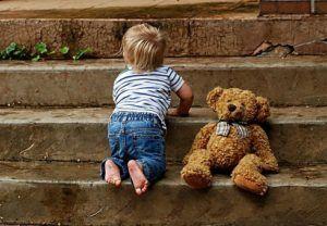 Kind mit Teddy auf einer Treppe